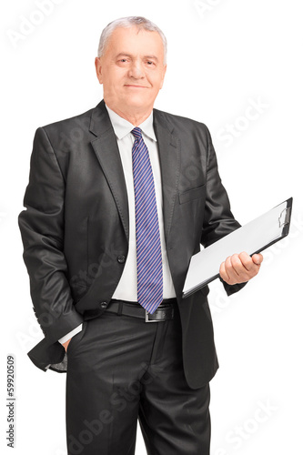 Smiling middle aged businessman holding clipboard