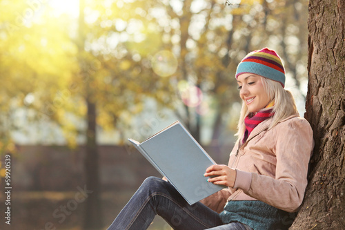 Young female with hat reading a book and enjoying in park