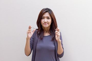 Woman with fingers crossed, plain blank background