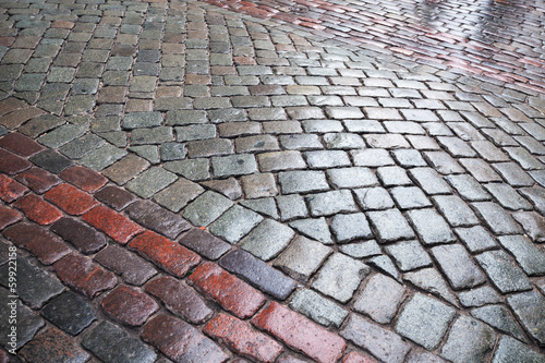 Background texture of wet granite cobblestone urban road