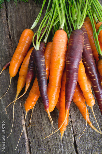 colored carrots on wooden surface