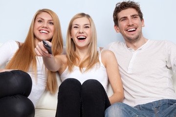 Group of young people watching tv at home