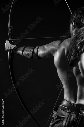 Young man with longbow prepare for a shot