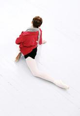 Beautiful ballerina make stretching on the floor