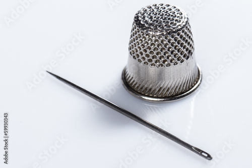 Tailoring. Needle and thimble on white background