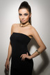 Vogue. Beautiful woman posing in black dress