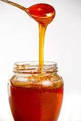 glass of fresh honey on white background