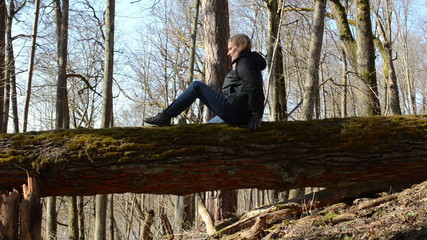 girl sitting on a log in forest twisted gently to the other side
