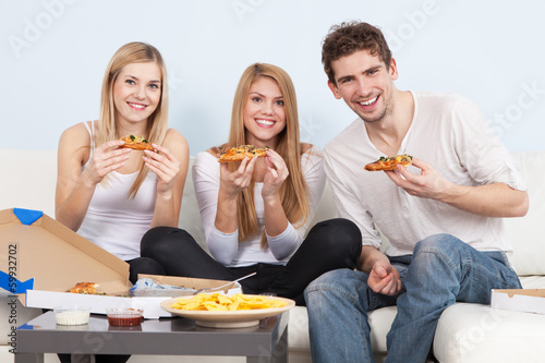 Group of young people eating pizza at home