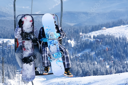 Two snowboarders sitting on ski-lift over the piste