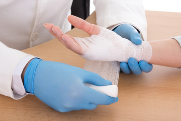 close up of young male doctor bandaging female hand