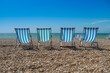 4 deck chairs on a pebble beach - 59937576