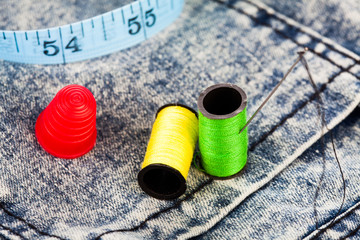 Cotton, needle, and a thimble on denim jeans