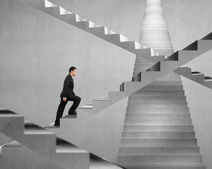 Businessman climbing on concrete stair maze