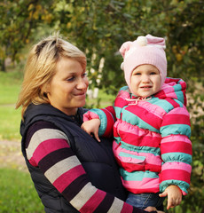 Happy mum with a daughter in autumn park