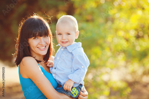 Portrait of beautiful happy smiling mother with baby outdoor