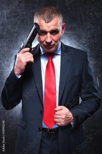 smiling old killer holding his gun and pulling his suit