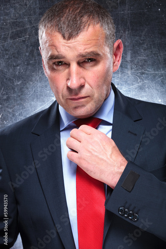 serious old business man fixing his red tie