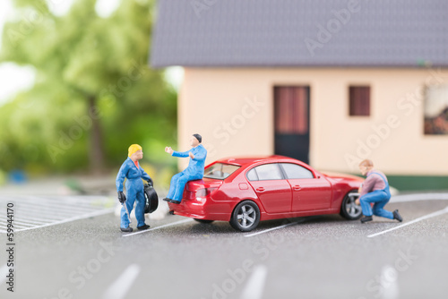 Miniature mechanic changing a punctured tyre