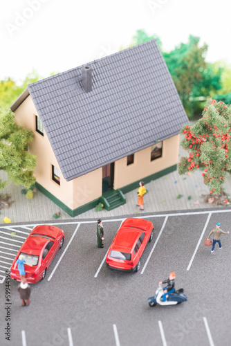 Miniature people, town house and a busy street model top view