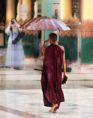 Yangon. Shwedagon Pagoda, monks pray at the foot of deities