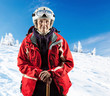 Senior woman in ski jacket and goggles outdoors. With path.