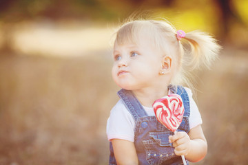 Little girl with candy walking in the summer park