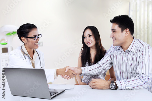 Medical doctor shaking hands with a couple