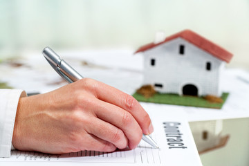 Hand filling out house buying contract.