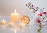 preparation for bath in white with towels, candles and orchid