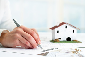Hand signing real estate contract.