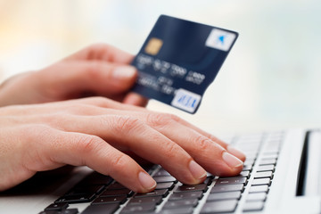 Hand typing on laptop with credit card.