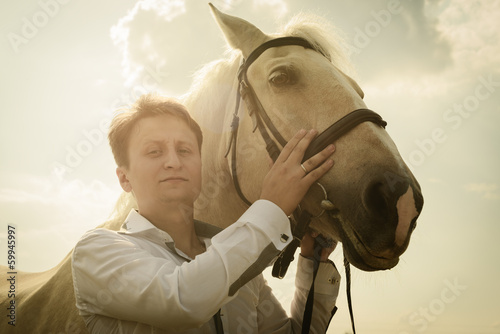 unusual groom at wedding on white horse outdoors