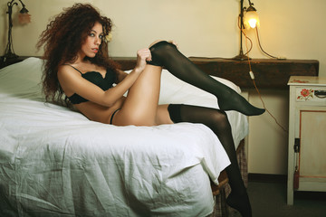 Beautiful brunette woman dressing on bed
