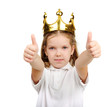 A little girl wears a crown and shows thumbs up.