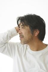 髪をかき上げる50代の男性
