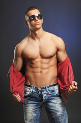 Sexy athletic man takes off his shirt