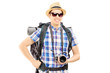 Male hiker with backpack and camera posing