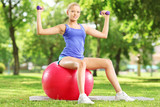 Blond female athlete in park sitting on ball and exercising