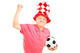 Middle aged sport fan with hat holding a soccer ball gesturing