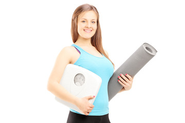 Smiling female athlete holding a weight scale and mat