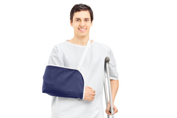 Smiling male patient in hospital gown with broken arm holding a