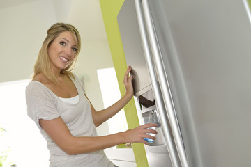 Smiling blond woman getting fresh water from fridge