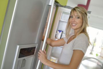 Smiling young woman opening fridge