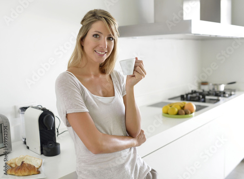 Cheerful young woman having coffee in kitchen