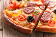 Pizza with slice on wood texture background
