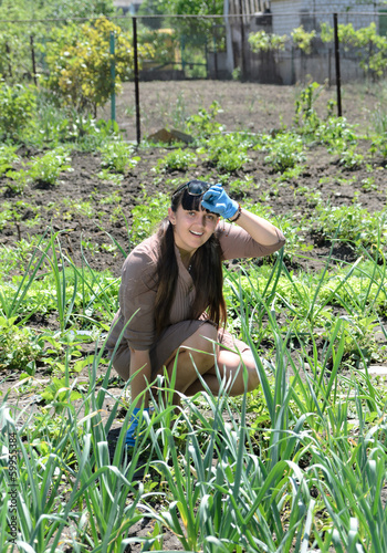 Happy young woman gardening in a warm sunny day