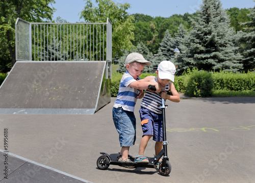 Two small boys arguing over a scooter