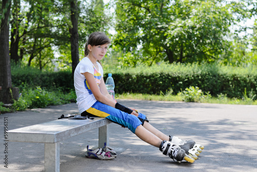 Cute teenager sitting and relaxing during skating