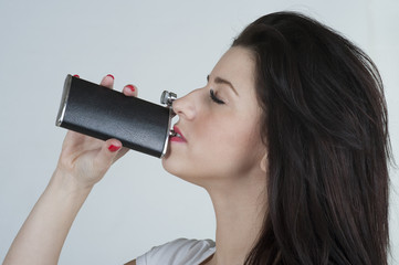 Young woman drinking from a hip flask